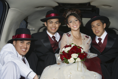 beautiful quinceanera sitting with three male friends in limousine