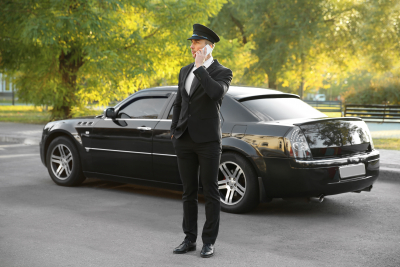 young chauffeur speaking by cellphone near luxury car on the street